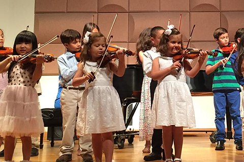 Children performing with violins at the Frost Preparatory Program
