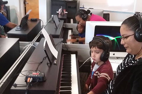 Students learning how to play the piano at the University of Miami
