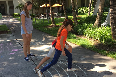 Children playing hopscotch at the University of Miami Coral Gables Campus